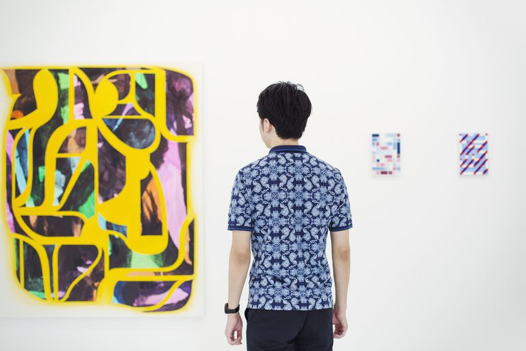 A man in an art gallery looks at abstract art.