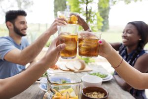 Friends toasting iced tea glasses at outdoor table