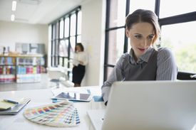 Female designer using laptop next to color swatches in office