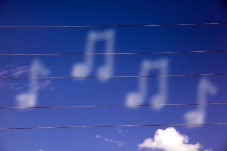 Clouds make the shape of music notes against a bright blue sky