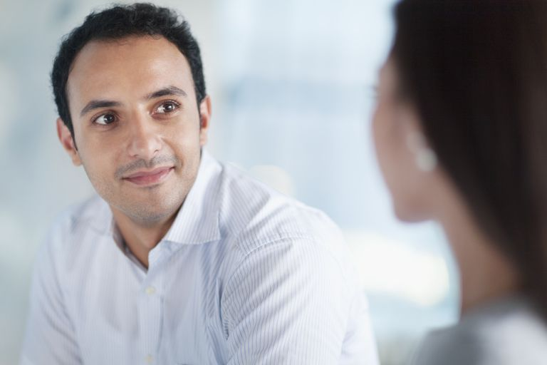 Young man looking at colleague in office