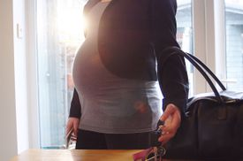 A pregnant woman picks up car keys from a table