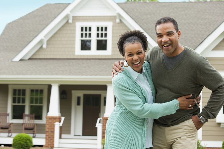 Black couple hugging in front of house