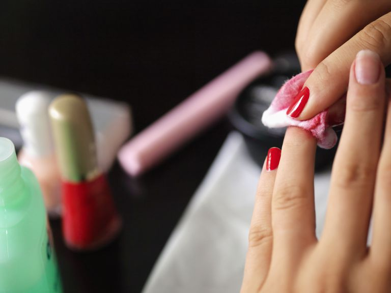 Woman removing her nail polish close up on hands and nails.