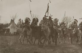 Group of Native Americans on horseback, sepia photograph.