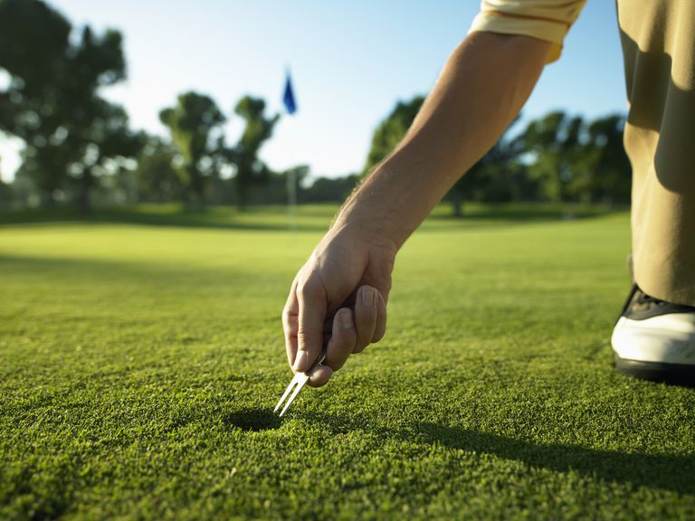 Golfer using a divot tool to repair a pitch mark