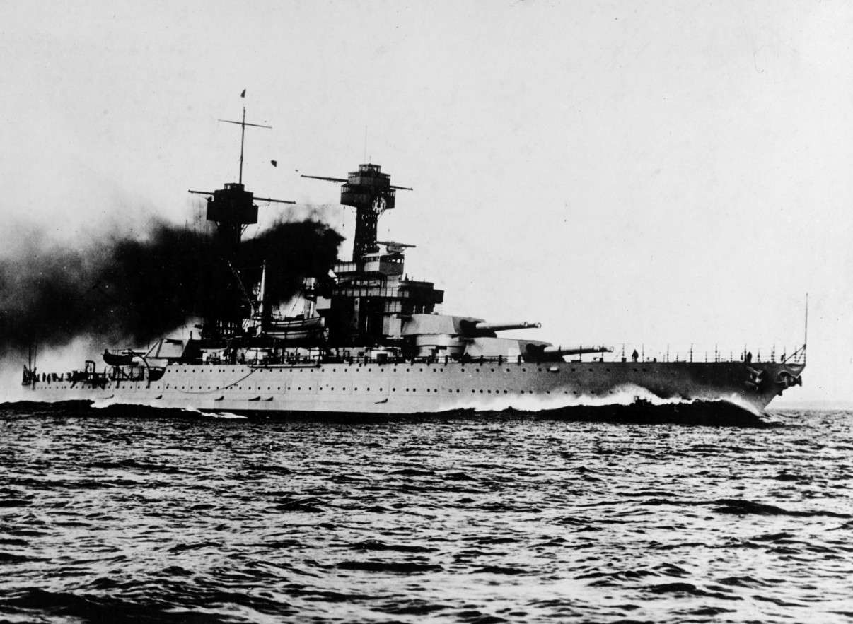 Battleship USS Colorado at sea with black smoke coming from funnels.