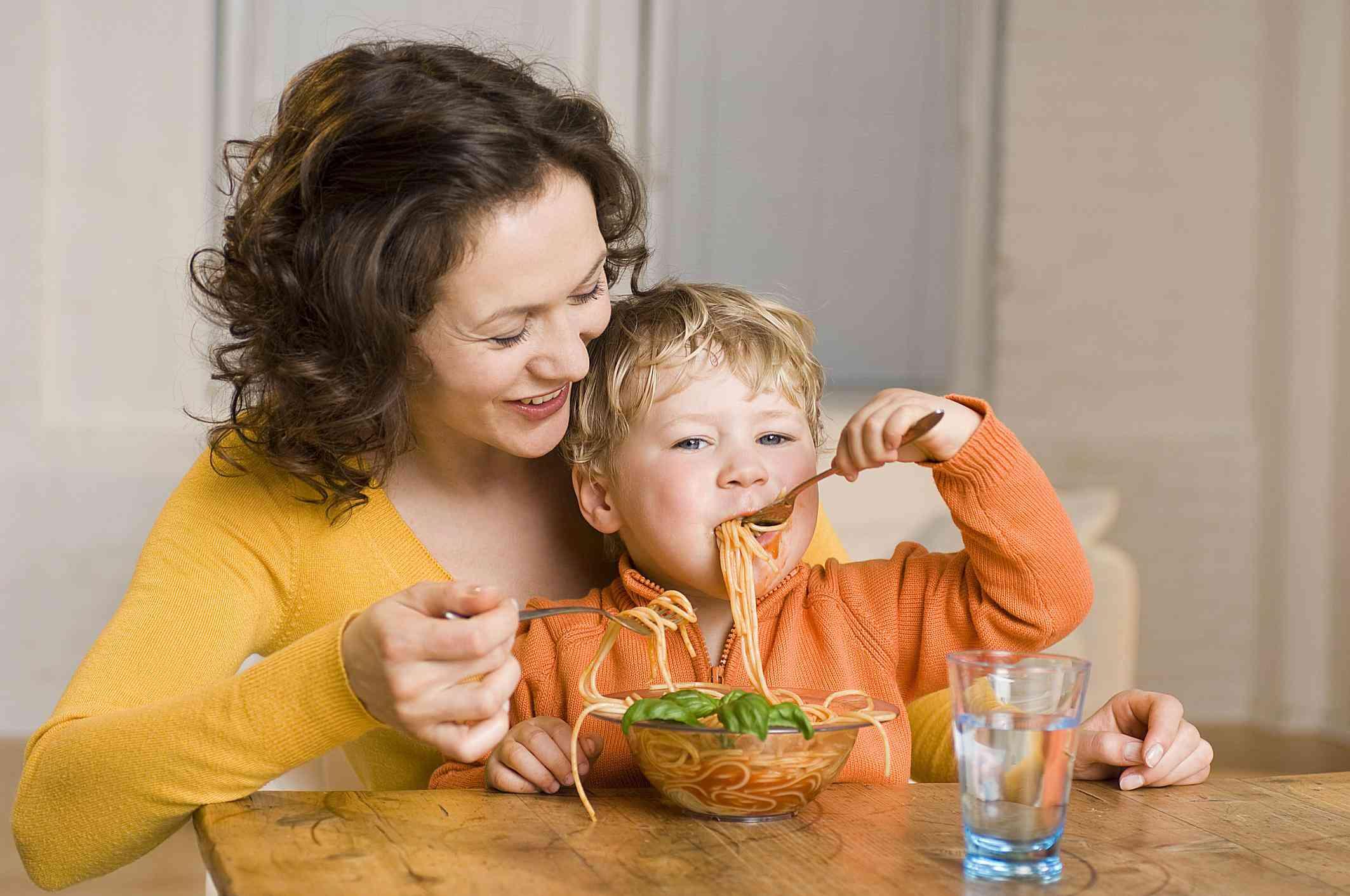 Niñera ayudando a un niño a comer pasta