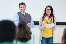 College student reading report with teacher to class