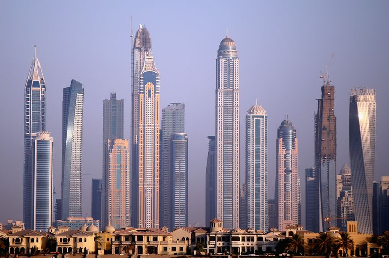 skyline of various shaped skyscrapers behind two-story homes along the shore