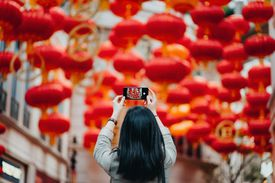Rear view of woman taking photos of traditional Chinese red lanterns with smartphone on city street