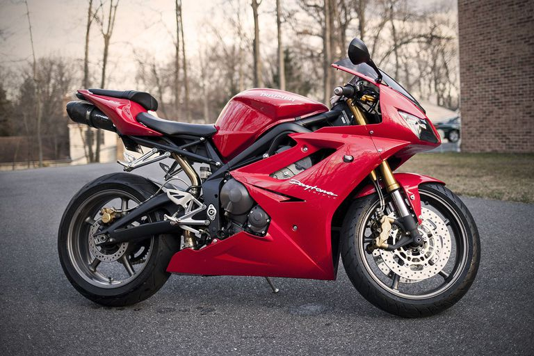 Triumph Daytona 675 motorcycle in red parked on blacktop.