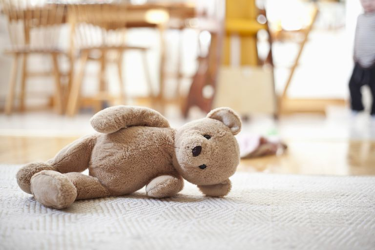 Abandoned teddy bear lying on carpet in house