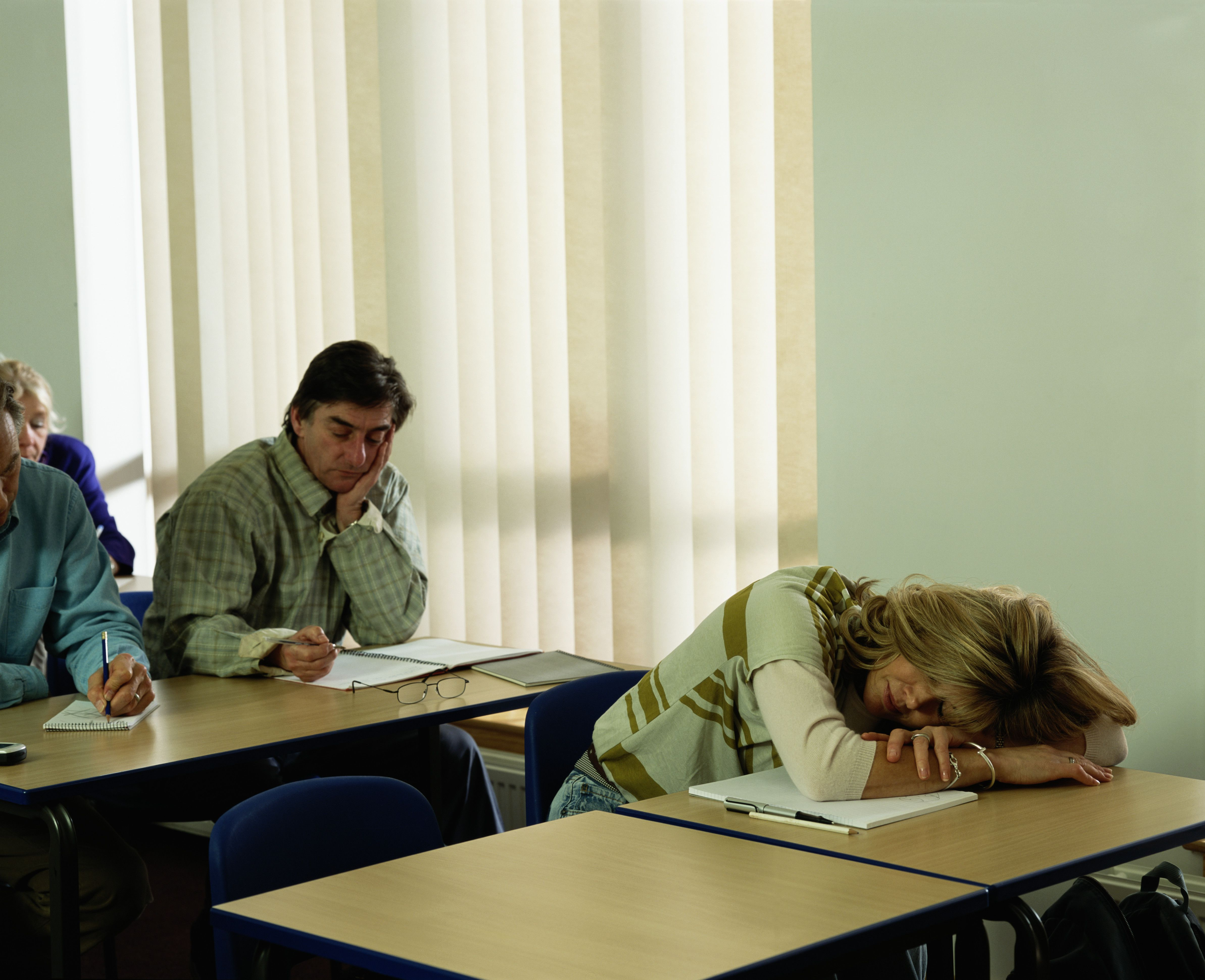 Mature students in class, woman sleeping on desk.