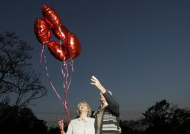 Senior couple with bunch of heart shaped balloons, looking up