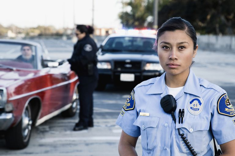 Policewomen pulling over man in convertible
