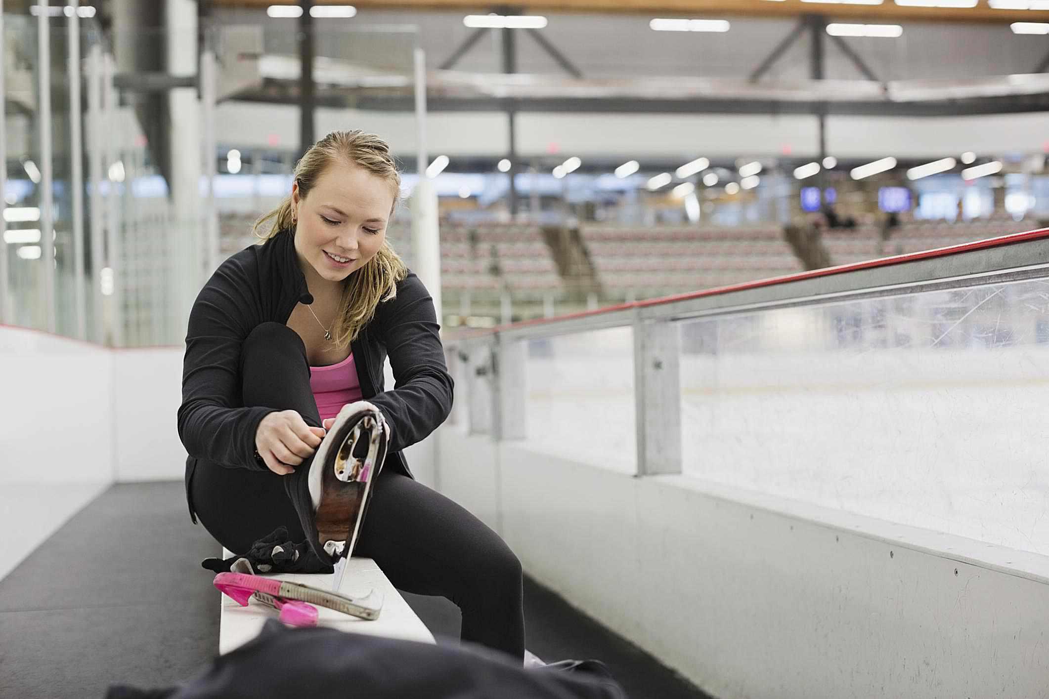 e7e800bc04c Female figure skater tying up skates in skating rink