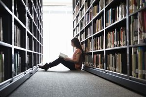 Girl reads book on in between two book shelves.