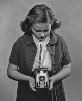 A picture of a girl using a Brownie camera.