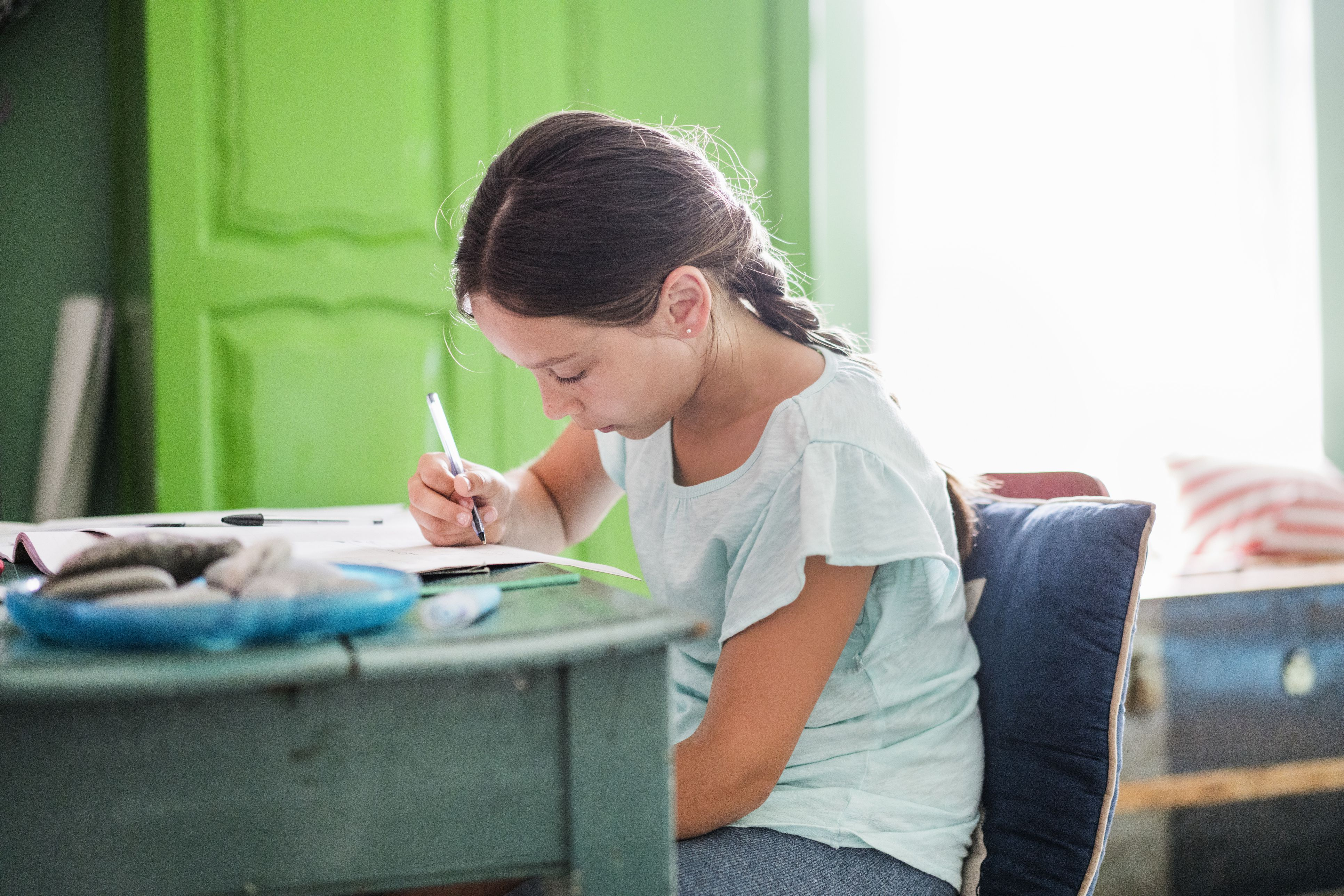 Concentrated girl doing homework at table