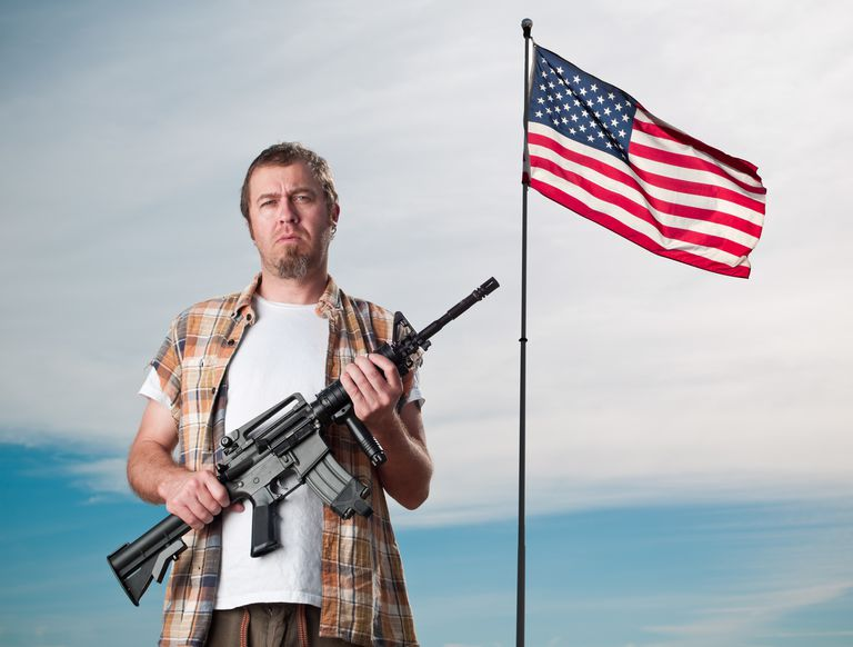 man with assault rifle in front of American flag