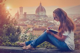 Young woman writing travel notes in Florence, Italy