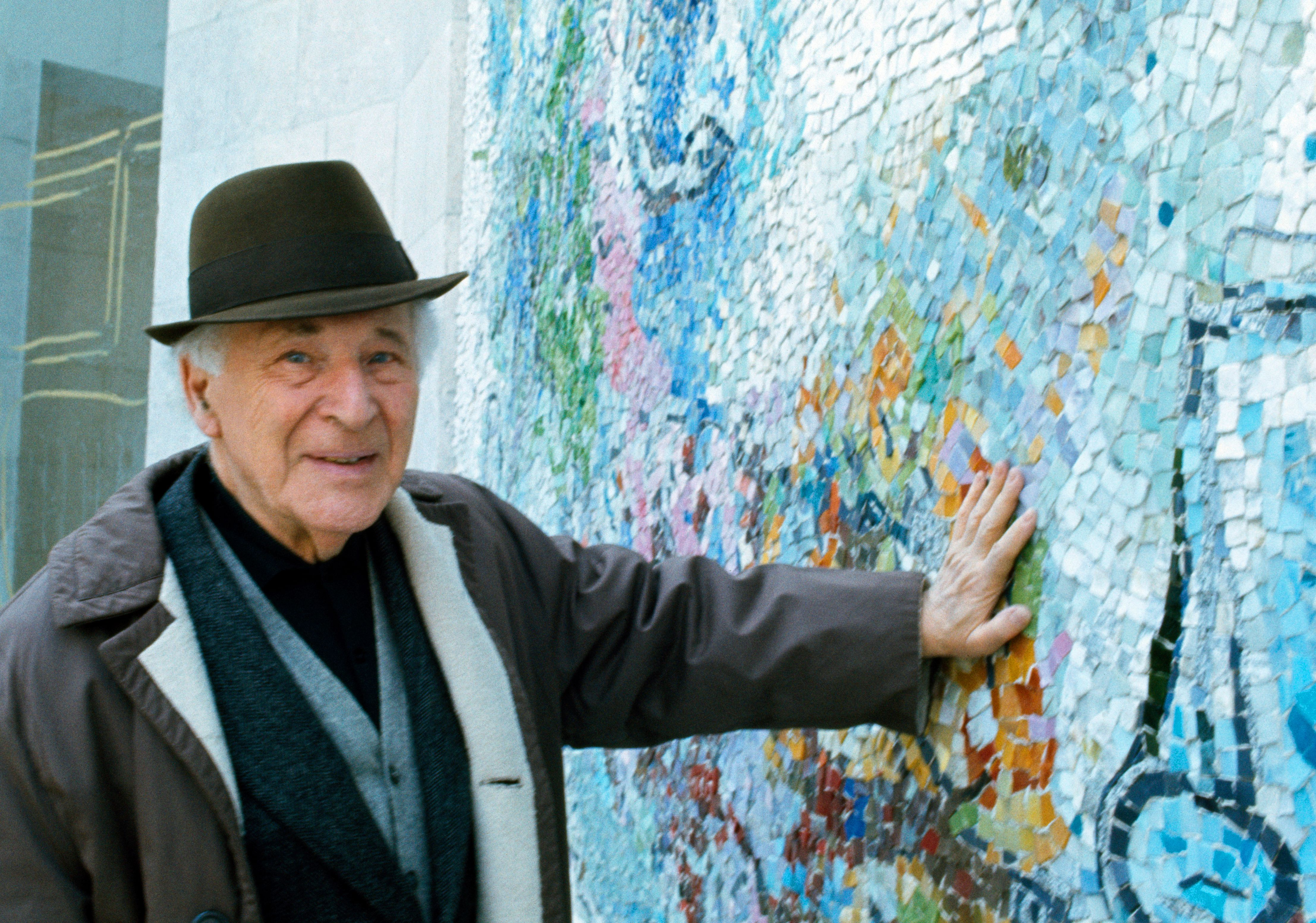 Artist Marc Chagall wearing a hat presses his hand against a wall with blue mosaic designs.