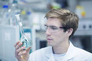 Scientist looking at liquid in beaker