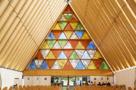 interior view of church, triangles of stained glass form a triangular entry wall, cardboard tubes take the shape of the triangular sides to form interior sanctuary walls