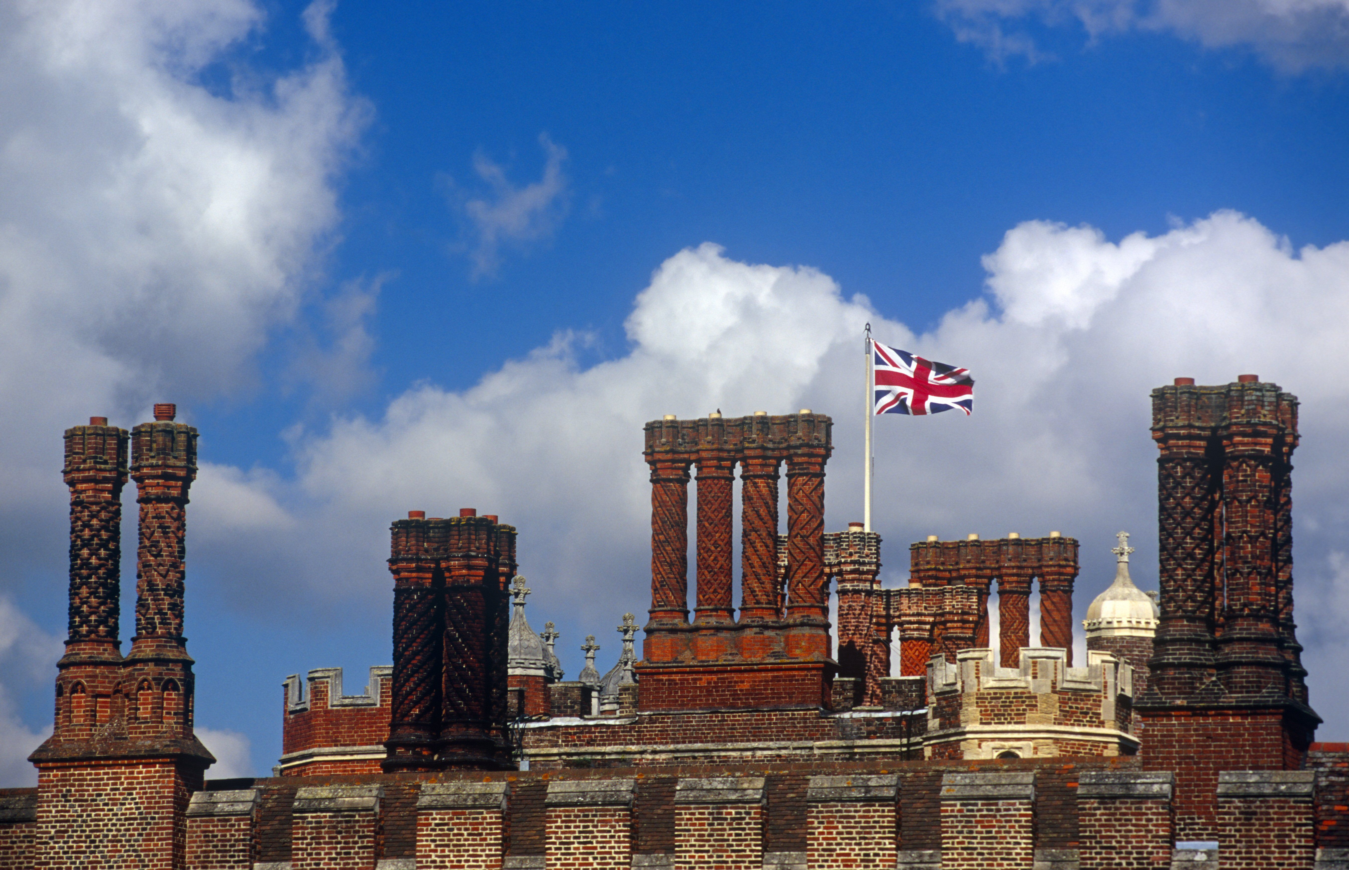 tall, ornate chimney extensions looking like carved pipes next to a Union Jack British flag