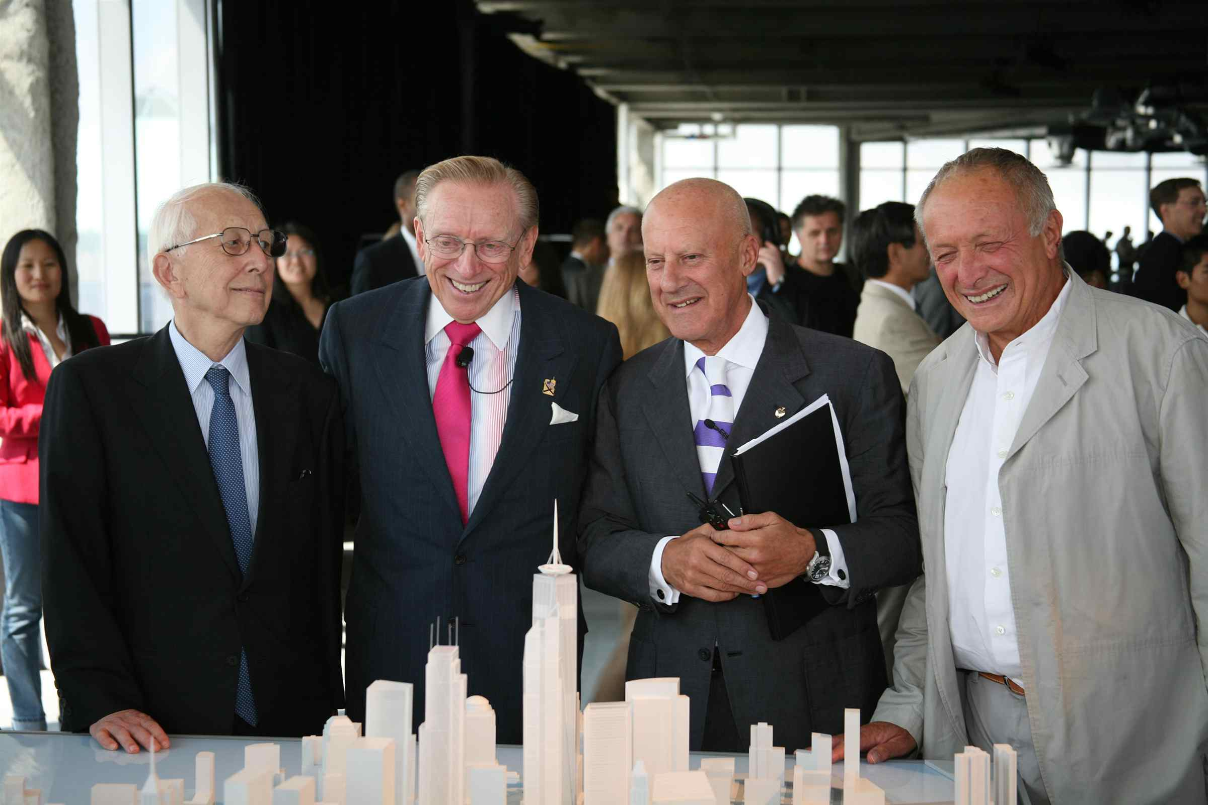 four older white men standing, smiling in front of a model with skyscrapers -- the third man holds a folder; the fourth man has no tie