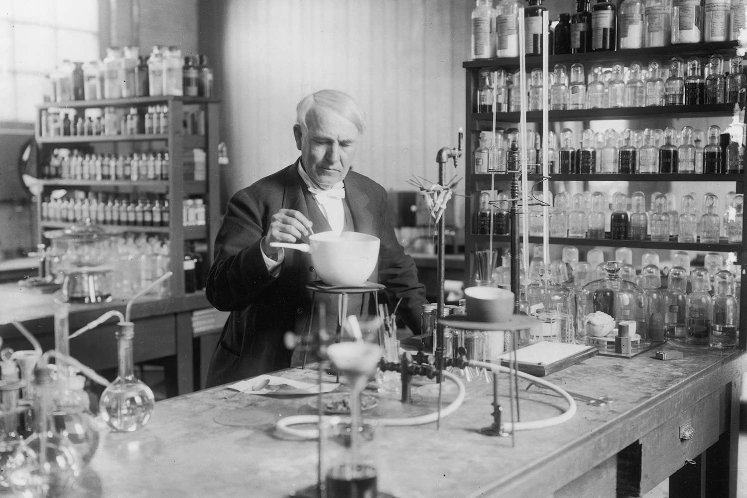 Black and white photo of American inventor Thomas Edison in his lab.