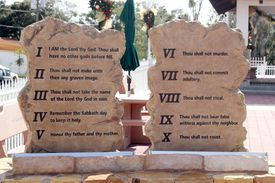 The Ten Commandment carved onto slabs of stone that are upright and sitting in the sun.