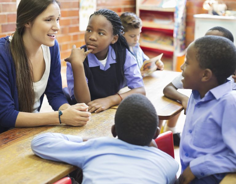 Woman speaking to young students in classroom