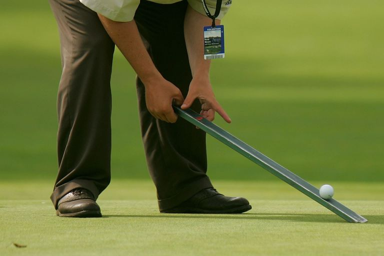 Taking the Stimp rating of a green using the Stimpmeter.
