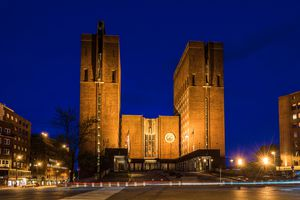 towering masonry building towers in evening, exterior lighting and a royal blue evening sky