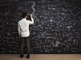 Man writes mathematical equations on chalkboard