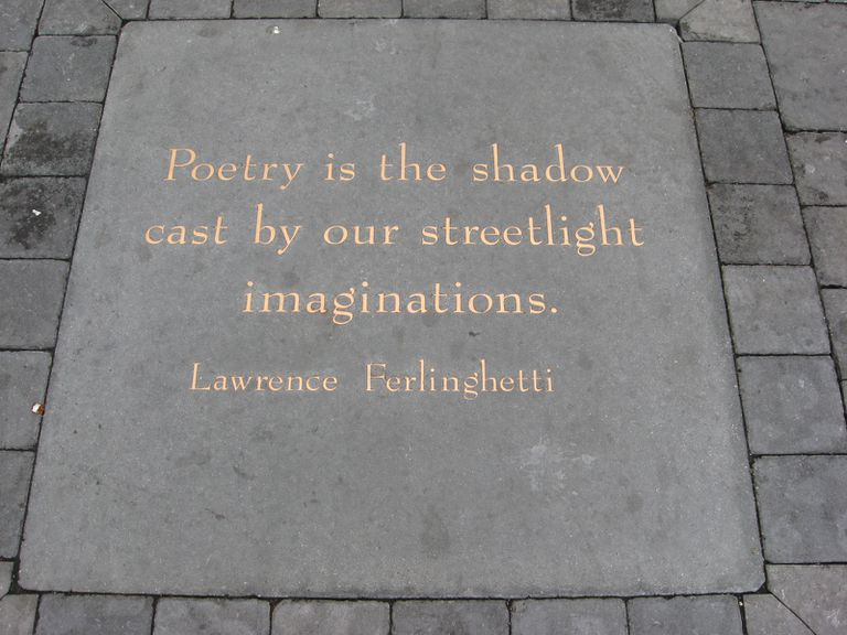 Quote about poetry in gold lettering on a stone.