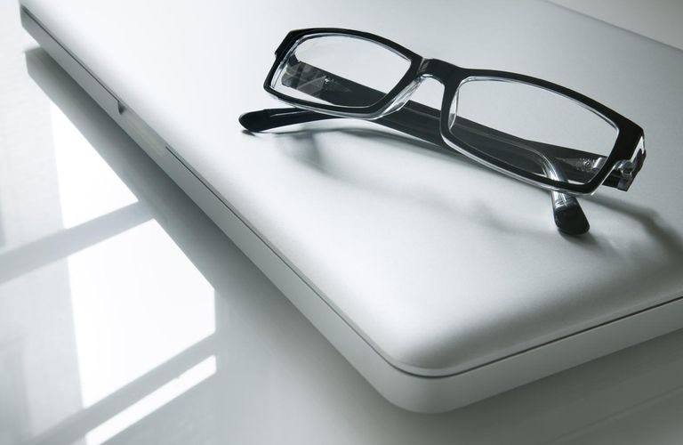 Reading glasses on closed laptop