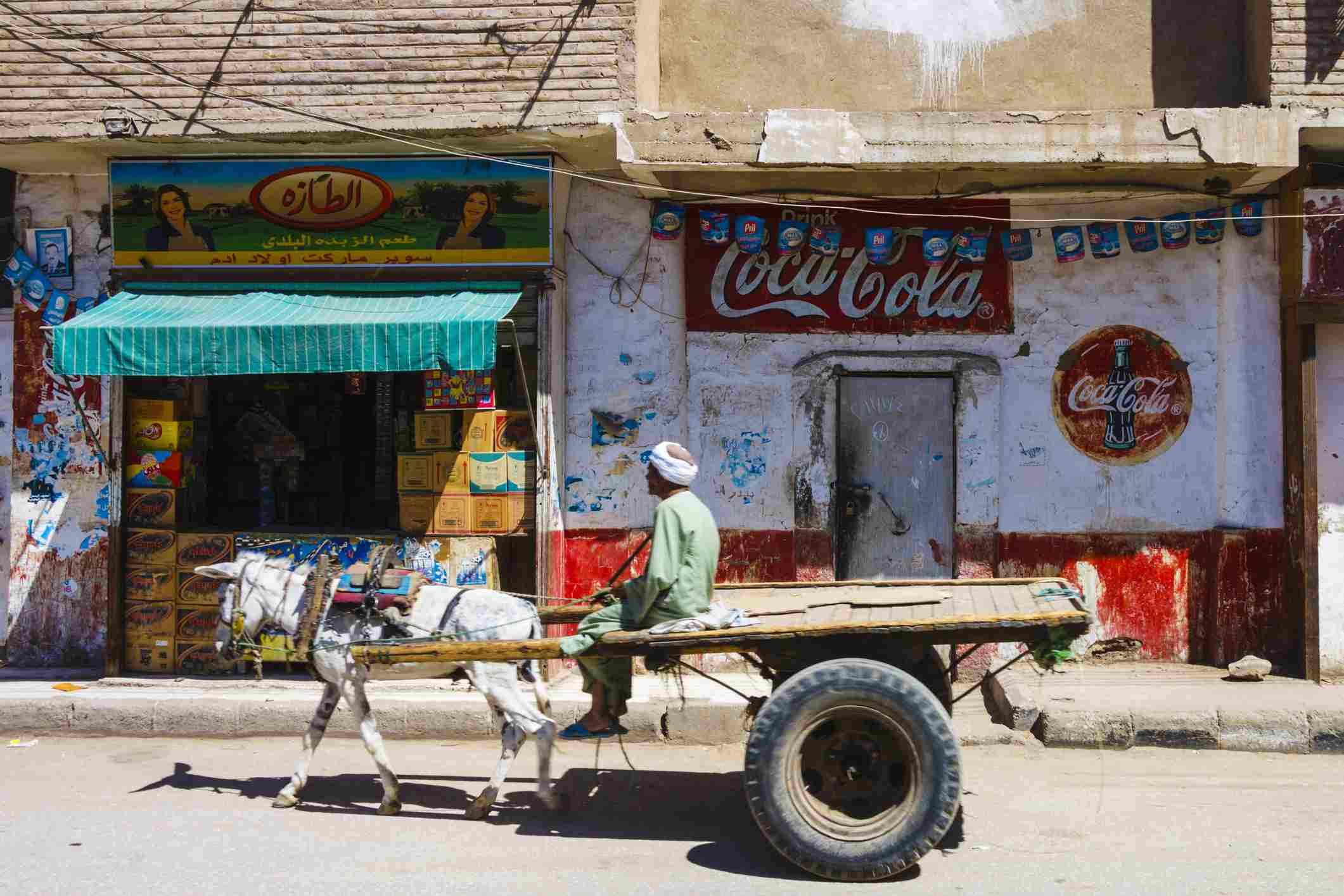 Man in a donkey cart drives past a shop with big Coca Cola painted sign