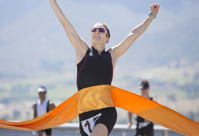 A runner breaking through the finish line