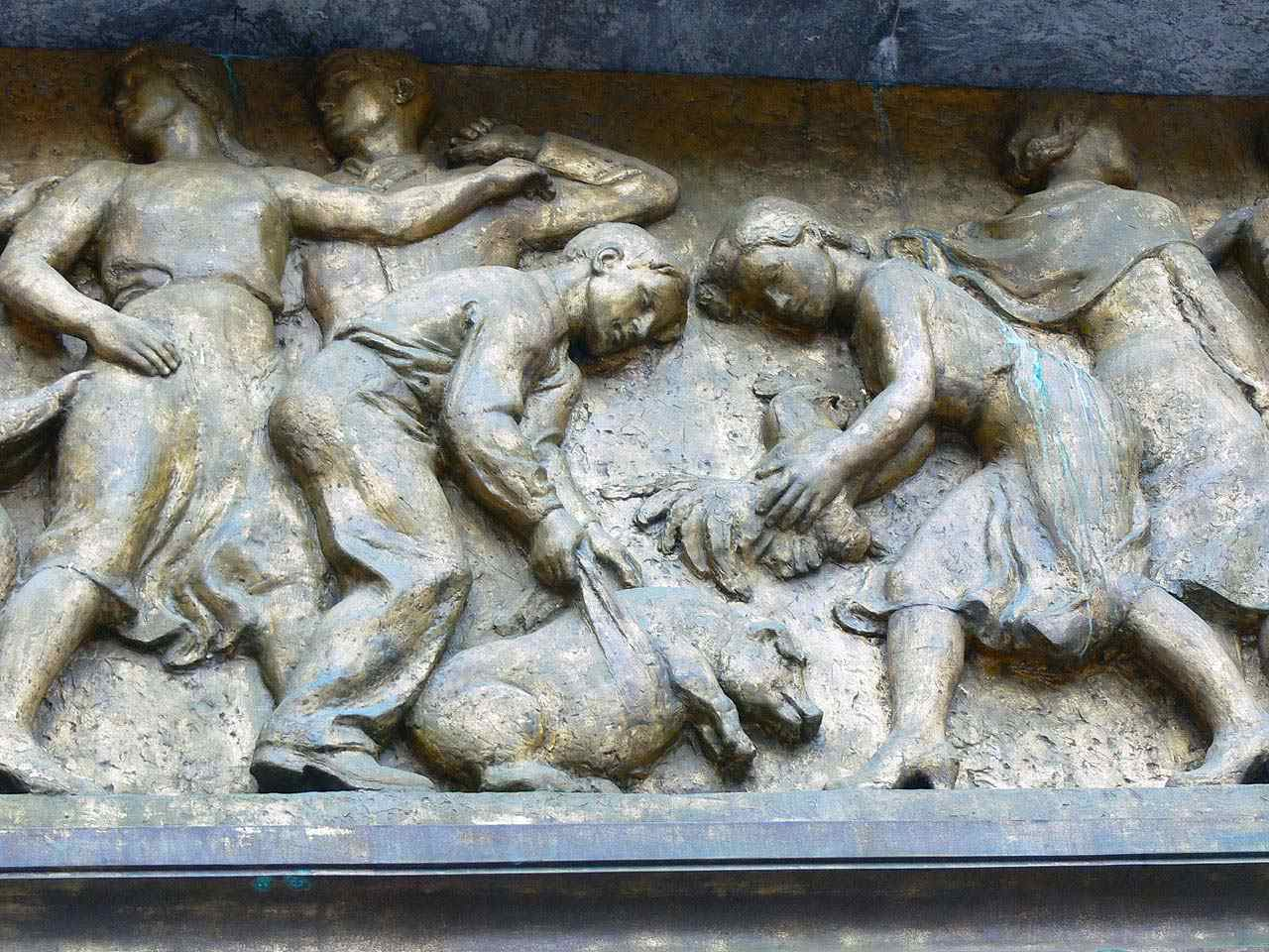 carved scene of people with a pig-like animal