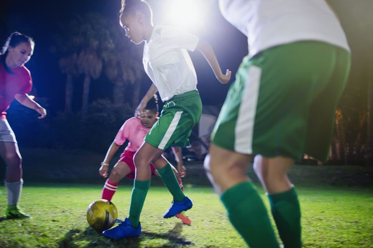 Young female soccer players playing on field at night
