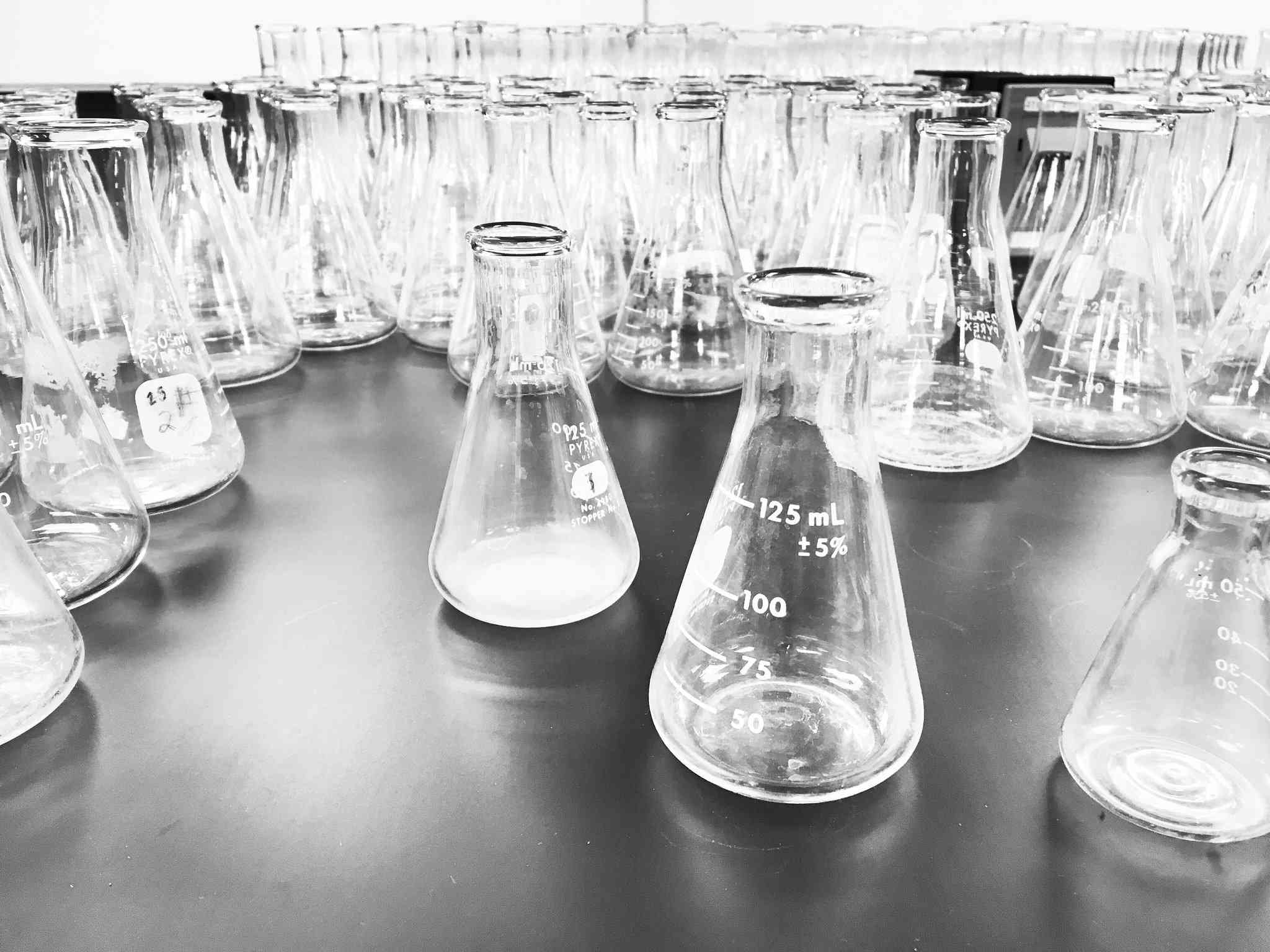 Multiple beakers on a gray table.