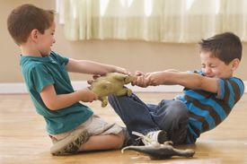boys fighting over toy dinosaur