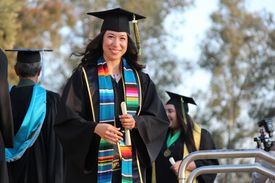 Young woman smiling at the camera after receiving her college diploma.