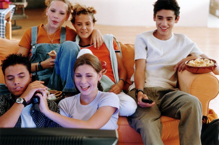 Five teenagers (14-17) watching television and eating snacks