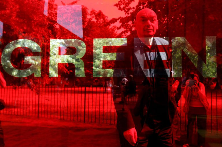 man with shaved head standing in red backdrop that says GREEN