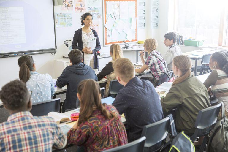 Maestra de secundaria en salón frente a alumnos.