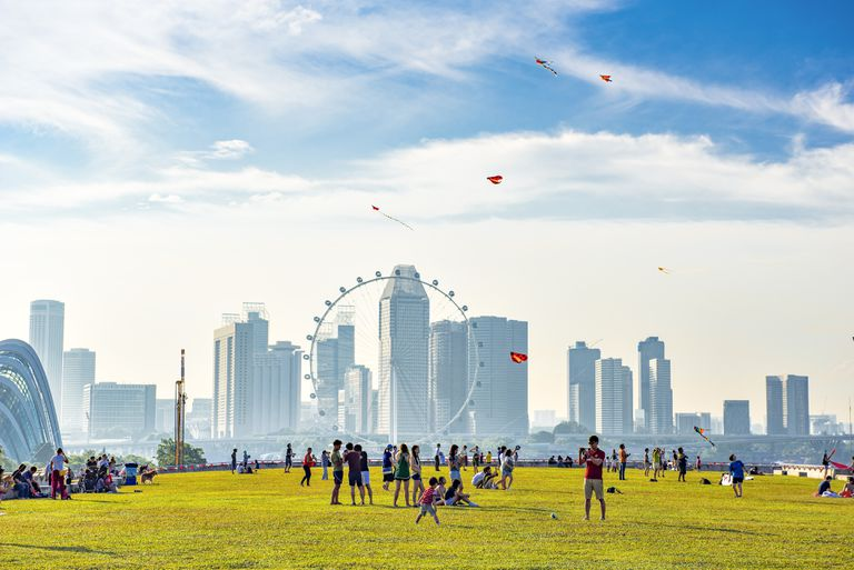People play in a park with the skyline of Singapore in the background